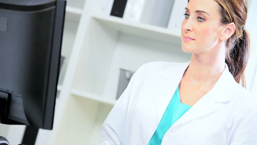 Young female medical doctor updating patient computer records - HD stock footage clip