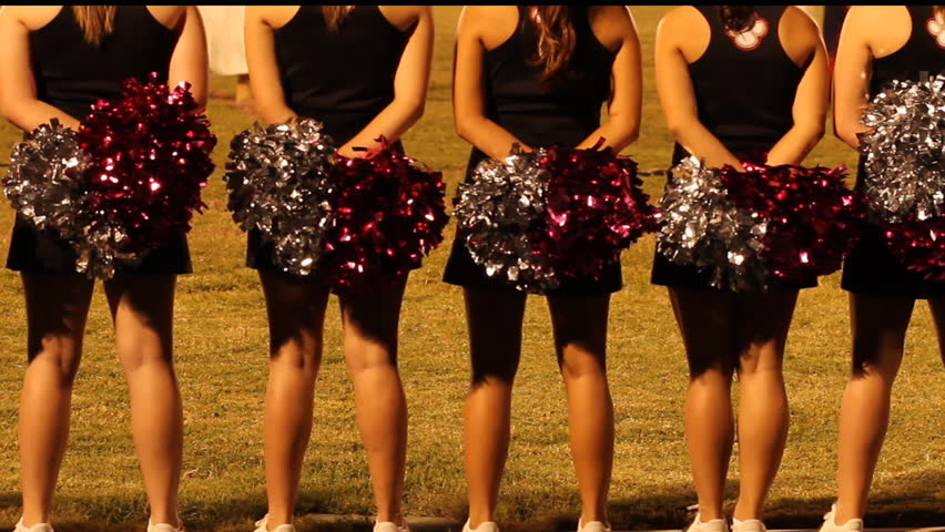 High school cheerleaders stand on sidelines, pompoms in hand, watch night football game. 1080p - HD stock footage clip