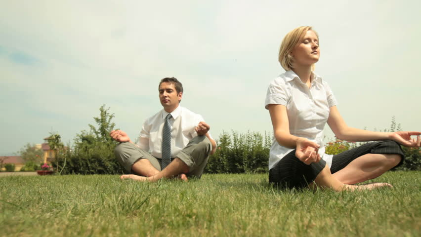 Young business people relaxing outdoors in lotus pose after long working hours - HD stock footage clip