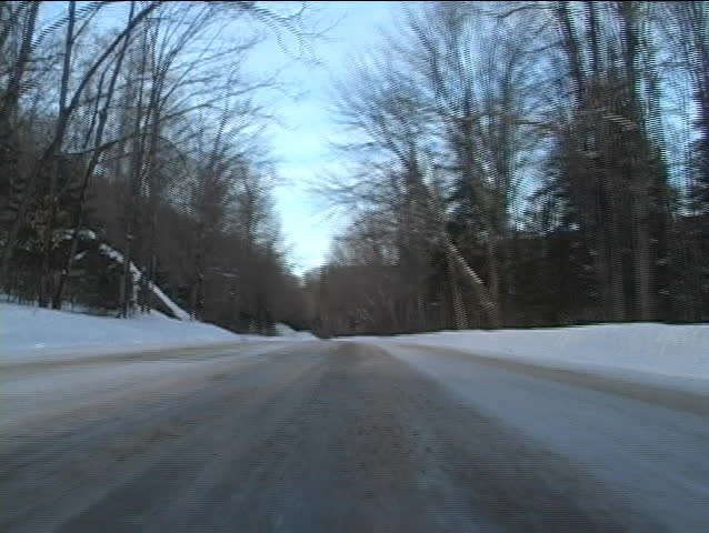 Low angle view of a car driving through remote area with roads filled with snow - SD stock video clip