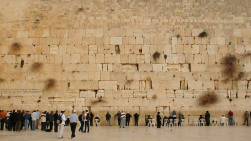 Wide shot. People praying at he Western Wall of Jerusalem.
