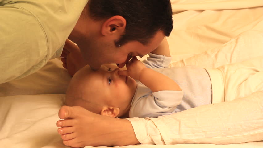 Young father kissing and playing with his baby laying on the bed between mother's feet - HD stock footage clip