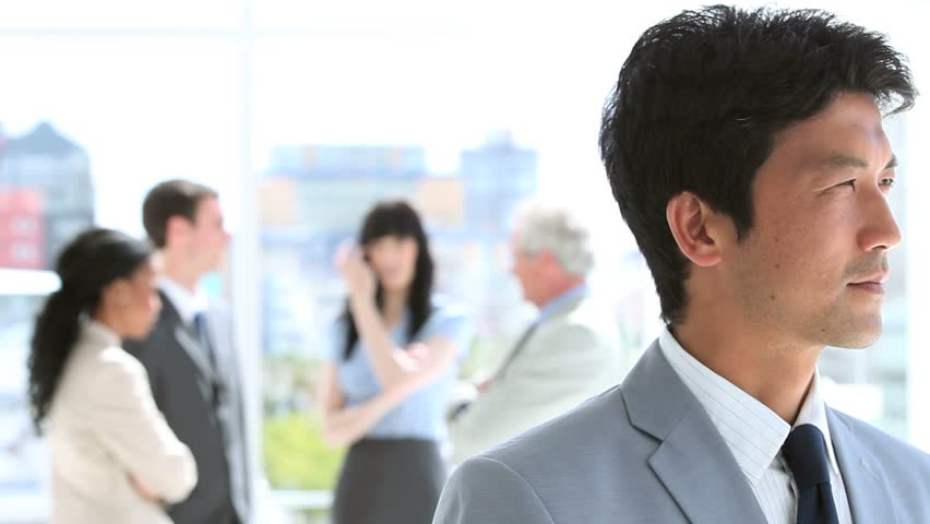Happy businessman standing upright in front of his team in a bright room - HD stock footage clip