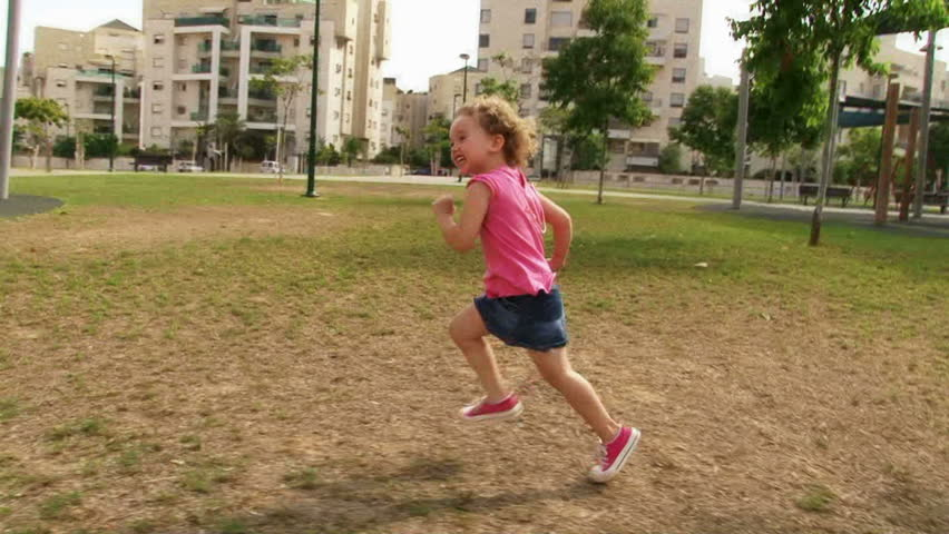 Little Girl running at playground / park in slow motion. Sequence.