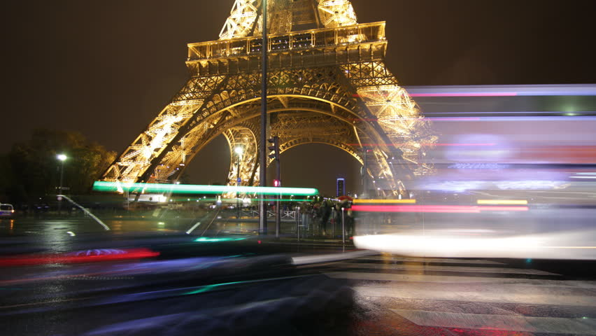 PARIS, FRANCE – APRIL 8th: Timelapse of Eiffel tower on rainy night on April 8th, 2012. Tourists and traffic passing by. Some raindrops on lens heighten the mood.