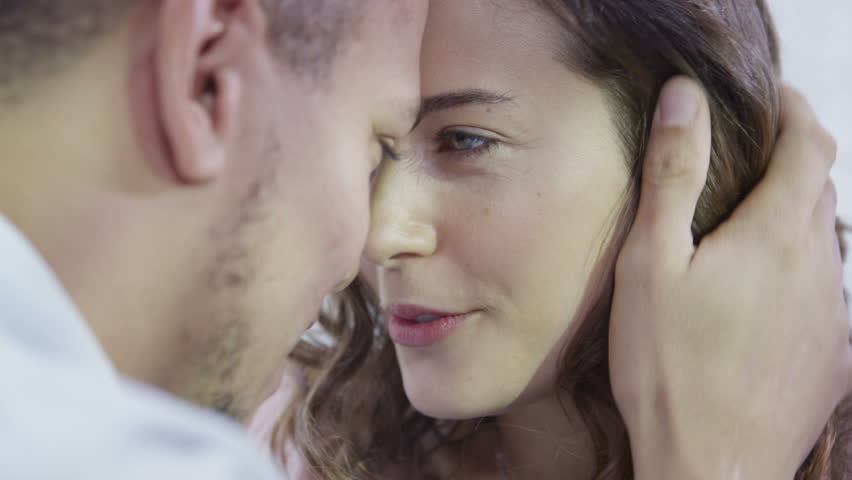 Happy young couple enjoying an intimate moment, laughing a lot and man gently strokes his partner's hair - HD stock footage clip