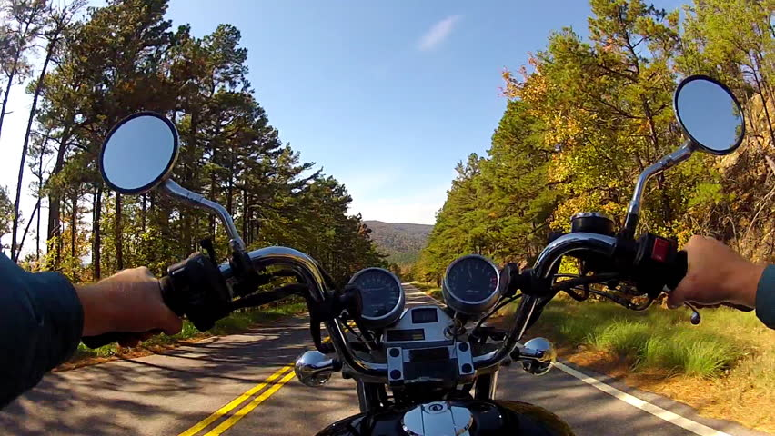 A wide angle point of view shot from a chest mounted camera on a motorcyclist riding a motorcycle on a forested mountain road. - HD stock video clip