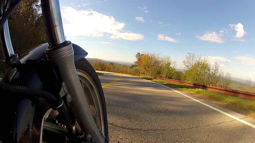 A low angle shot of the speeding front tire of a motorcycle on a rural road.  - HD stock video clip