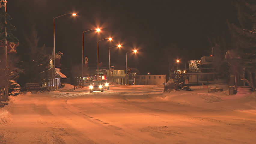 HOMER, AK - CIRCA 2012: Minimal traffic at night in a small town on snow-covered roads in the middle of winter. - HD stock footage clip