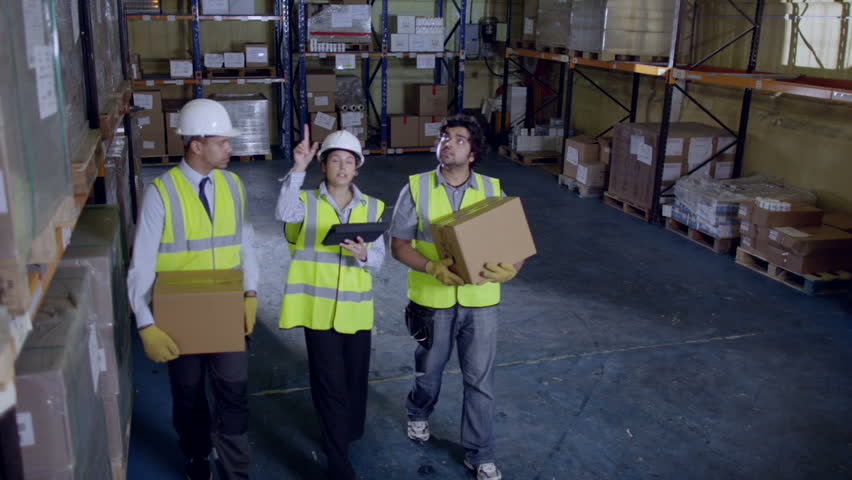 3 workers are walking along the aisle of a warehouse and checking their inventory. Two workers are carrying boxes and their female manager is giving them instructions. Slow motion.