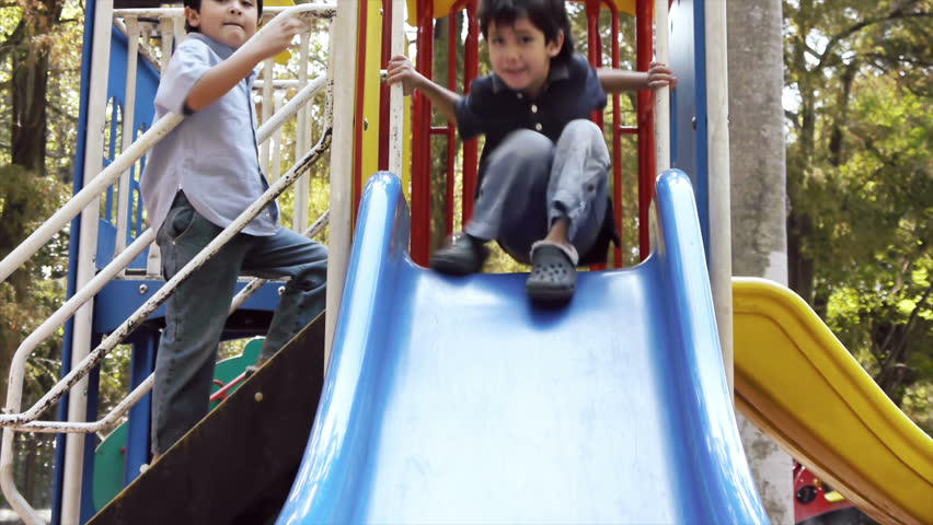 Two Latino Kid Brothers Playing on a Public Park Slide Seen from the Front.