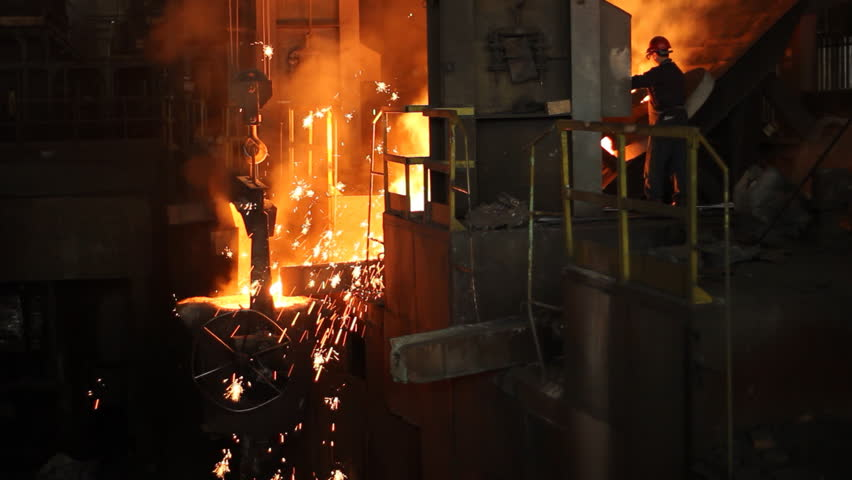 Hard work in the foundry, worker controlling iron smelting in furnaces, too hot and smoky working environment - HD stock footage clip