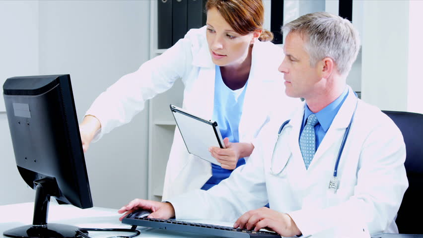 Caucasian Male medical consultant with young female doctor updating patient computer records using tablet shot on RED EPIC