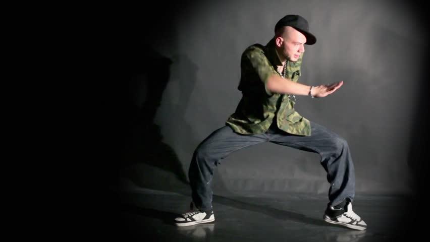 Hip-hop dancer in cap dances in photo studio with black background
