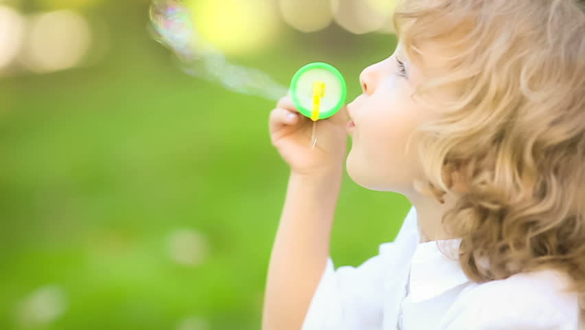 Happy child blowing soap bubbles in spring park. Slow motion - HD stock video clip