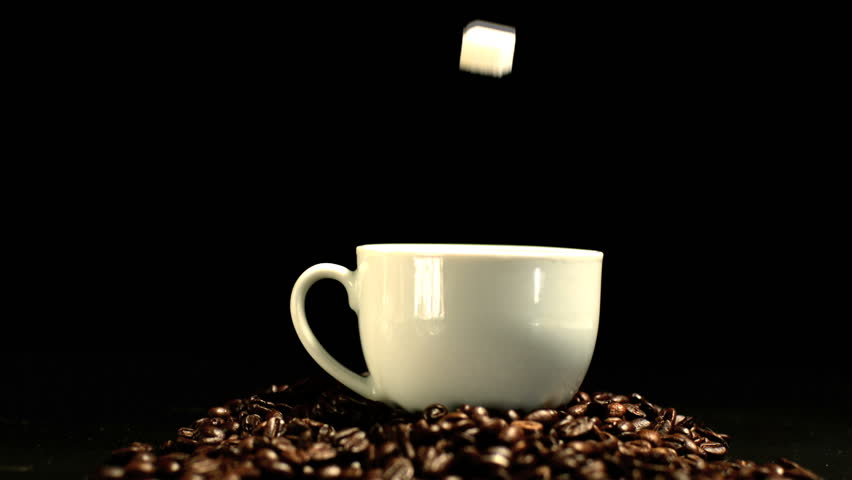 Sugar cube falling in coffee cup and splashing in slow motion