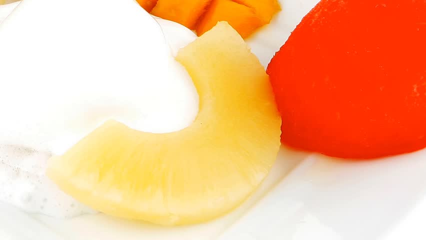 tropical fruits and ice cream on white plate hidef slow motion intro