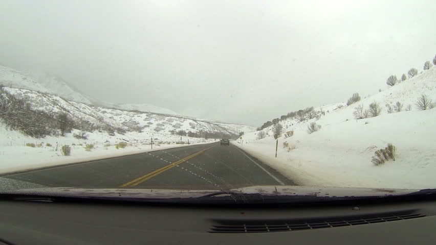 Winter snow storm driving mountain road. Driving a car on rural country road in winter. Snow and ice on highway and near mountains and hills. First person point of view through windshield. - HD stock footage clip