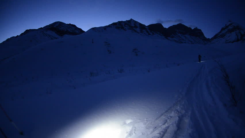 A hiker skis along a path in the frozen Alaskan wilderness, guided by his flashlight in the early dawn hours with very little light