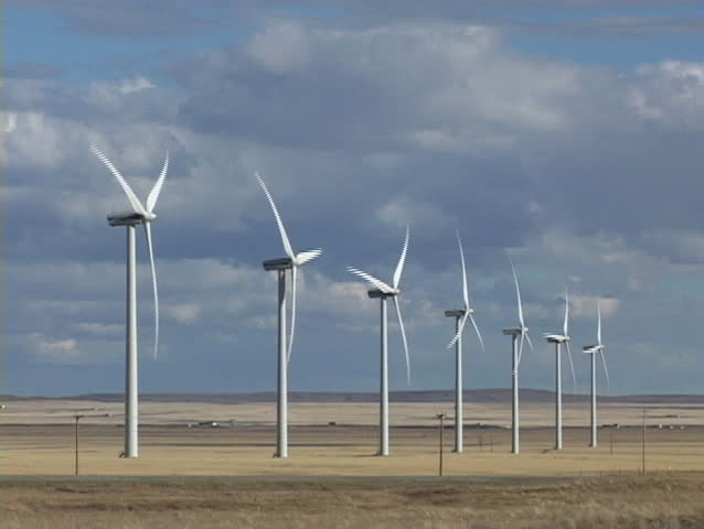 Row of seven wind turbines with passing truck