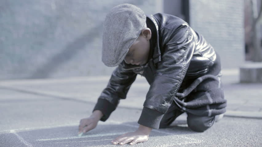 African American Black kid with hat drawing a number in chalk on the floor