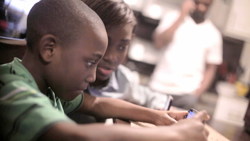 African American Black Kid playing video games while his father is on the phone in the background - HD stock footage clip