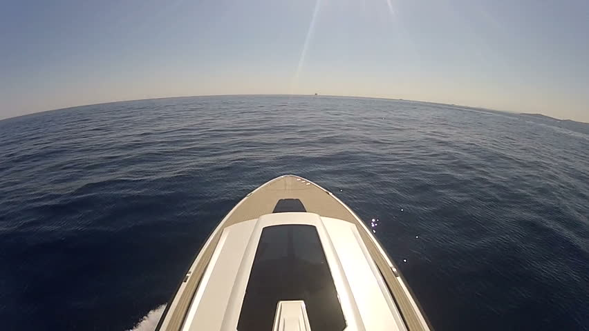 Wide and high angle view above deck of large modern power boat at very high speed, making turn to port, left, towards land.  GoPro HERO2 with no stabilisation applied - HD stock video clip