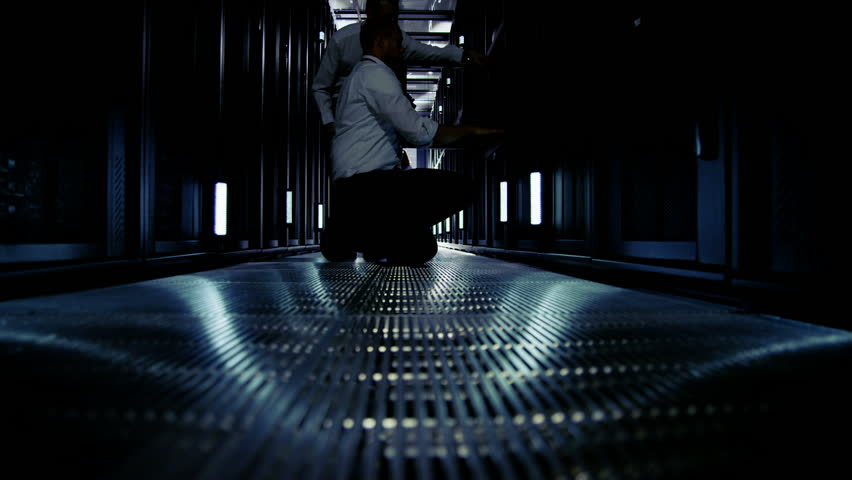 Time lapse of a team of people working in a data center with rows of server racks and super computers. They are looking into data cabinets and checking cables and other equipment.
