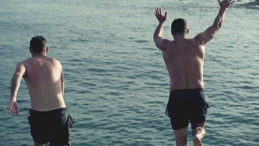 Young men jumping, swimming in the sea, slow motion shot at 240fps