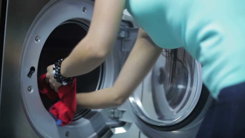 Woman taking clothes out of the washing machine