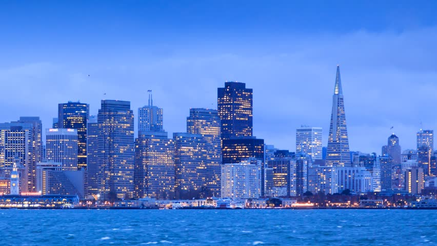 San Francisco skyline from twilight to night. View from Treasure Island. Zoom in on downtown. Timelapse.