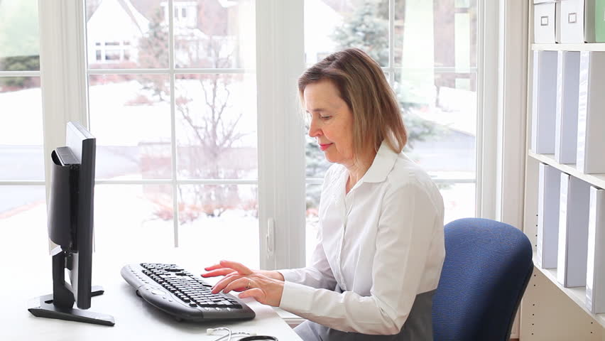Middle Aged Caucasian Female General Practioner Doctor Typing On A Desktop Computer In Her Office