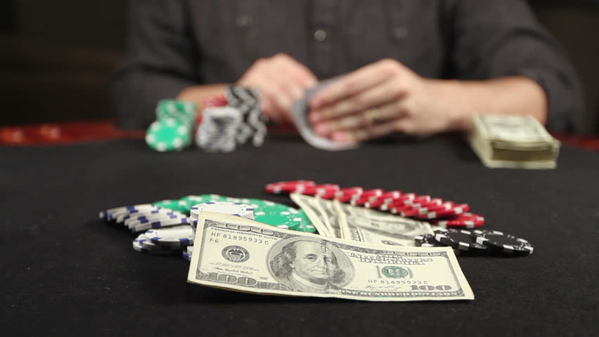 A gambler at a poker table peeks at his cards 'and bets a stack of chips - HD stock video clip