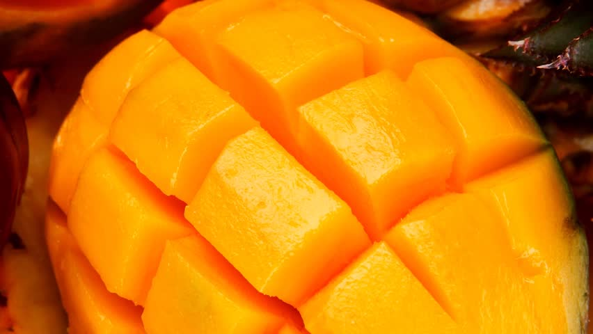 diet food - a lot of fresh raw tropical fruits include pineapple red plum and green mango in orange colander