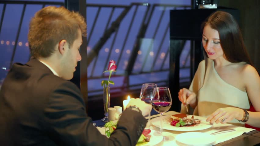 Young woman eats cake and man prefers vegetables during dinner at restaurant - HD stock video clip