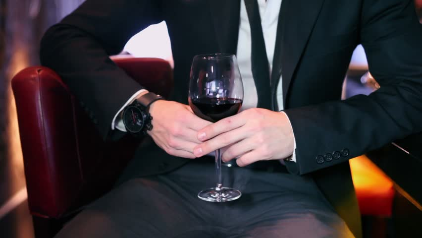 Man in black suit hold glass with red wine and drinks it, closeup - HD stock video clip