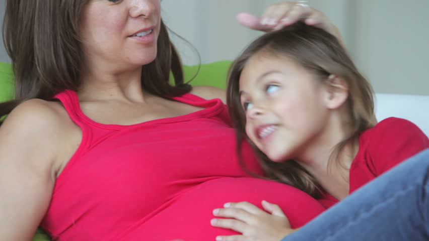 Daughter listening to pregnant mother's belly. Shot on Canon 5d Mk2 with a frame rate of 30fps