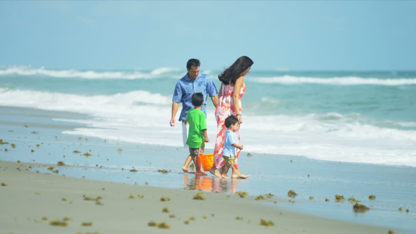 Attractive Hispanic family playing with young children on sandy beach shot on RED EPIC - HD stock video clip