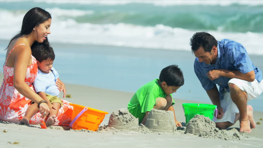 Happy Hispanic parents helping sons with sand castles on summer beach shot on RED EPIC - HD stock video clip
