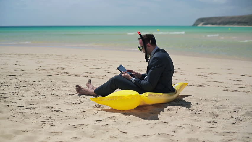 Businessman in diving mask working on tablet computer on the beach