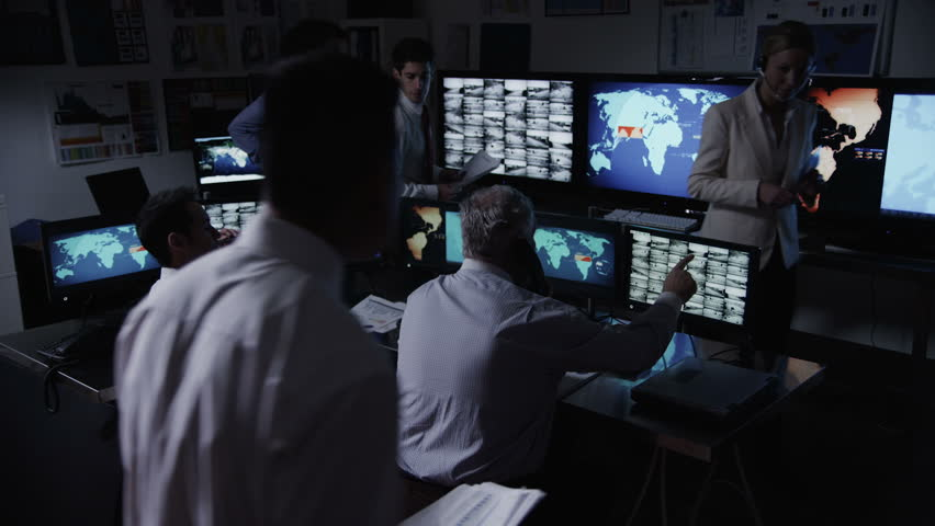 A busy team of security personnel are manning the stations within a busy system control room.  - HD stock video clip