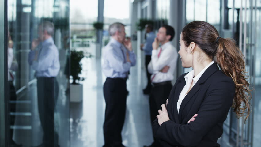 Portrait of an attractive and confident young business woman standing in a light and modern office building. The rest of her team can be seen chatting together in the background.
