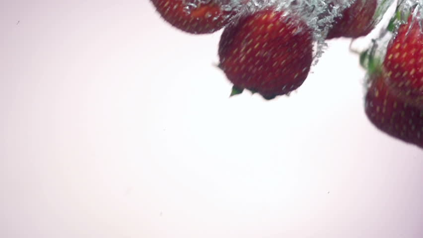 fresh strawberry dropped into water with splash on backgrounds