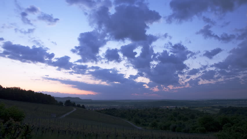 Wide angle time lapse shot of a rural sunrise with heavy clouds, going from almost night with dark blue to bright rays of sun seen through the clouds.   - HD stock video clip