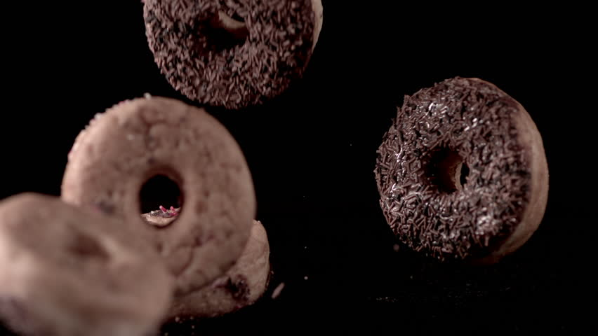 Lots of sweet but sinful iced donuts falling in slow motion and bouncing off each other on a black background.