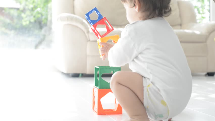 Little cute boy playing at home with toy cubes - HD stock footage clip