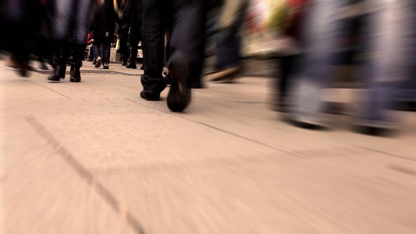 Pedestrian traffic on a city sidewalk in low profile shot / HD1080 / 30fps