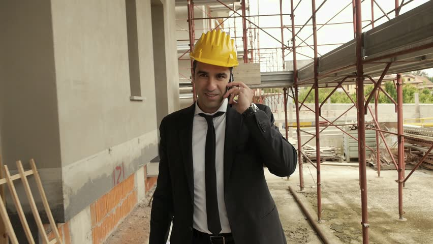 Profession, business and telecommunications, architect talking on cell phone and walking in construction site under building scaffolding. Steadicam shot