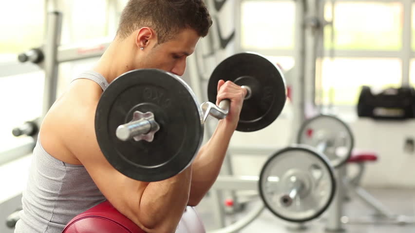 Man working his arms at the gym, He lifting the dumbbells and working his biceps.