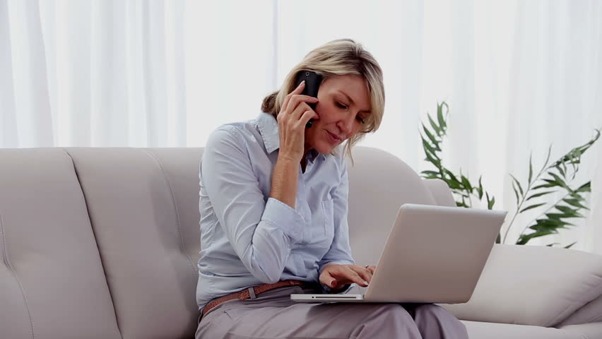 Woman on the phone using laptop in her living room